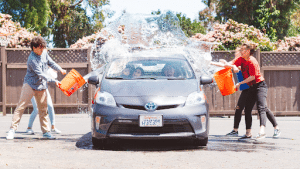kids throwing buckets of water on a car for a car wash