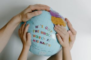 """two sets of hands on a globe with the words """"he's got the whole world in his hands"""" stickered on it"""
