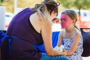 woman painting a young girls face pink as a face painting booth