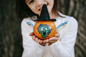 girl holding small decorated pumpkin