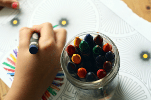 close up of kids hand coloring with crayons