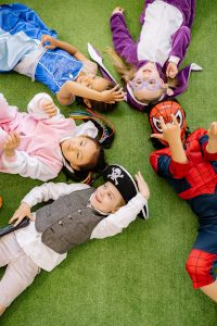 group of kids in costumes lying on the ground