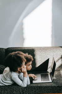 two kids lying on couch, scrolling on laptop