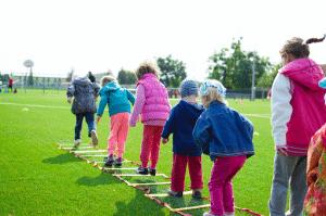 kids running through an agility ladder