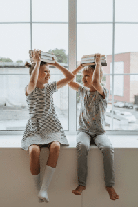 two kids with books on their heads