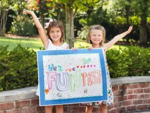 two girls holding a we love fun pasta decorated sign