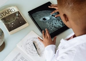 young student researching space on his tablet